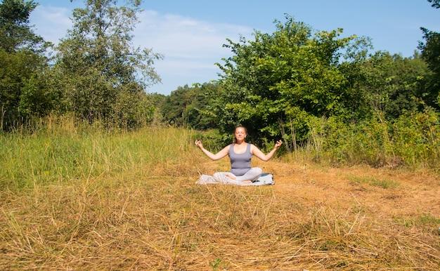 Uma mulher faz ginástica na natureza. meditação de ioga