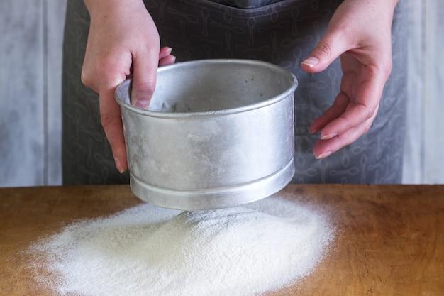 Uma mulher faz macarrão caseiro com farinha, ovos e sal. estilo rústico.