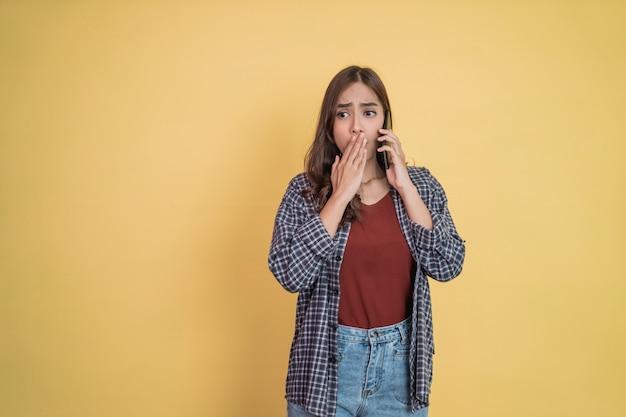 Uma mulher faz uma ligação com um telefone celular com um gesto de surpresa com copyspace