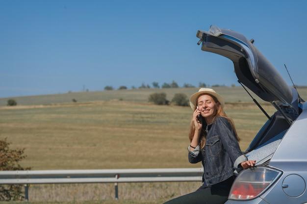 Uma mulher faz uma ligação. o turista parou na estrada. viajar de carro. ligando para reparos de carros