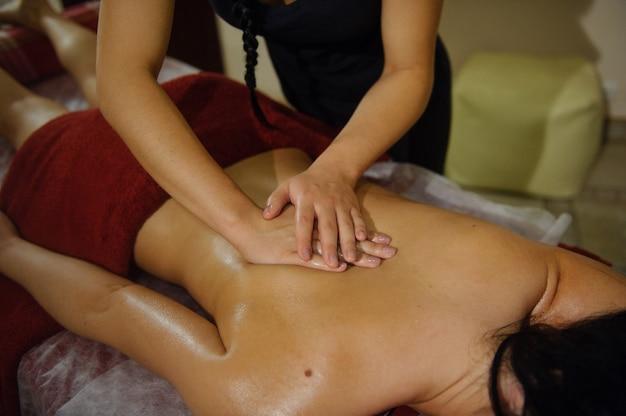 Uma mulher faz uma massagem com as duas mãos nas costas de uma garota deitada em um centro de spa.