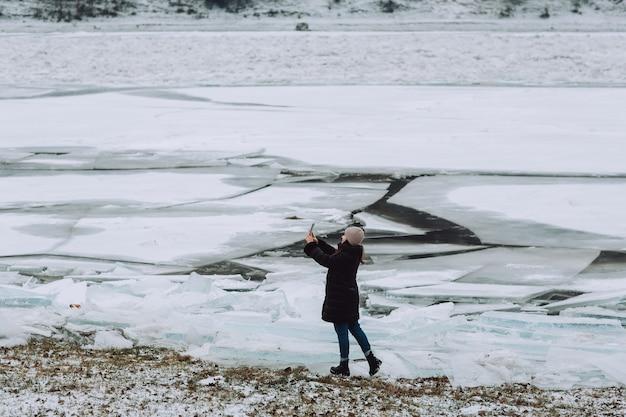 Uma mulher faz uma selfie ao telefone no inverno na margem de um rio congelado com blocos de gelo.