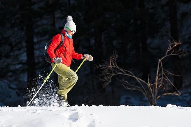 Uma mulher faz uma viagem com raquetes de neve sozinha na primavera