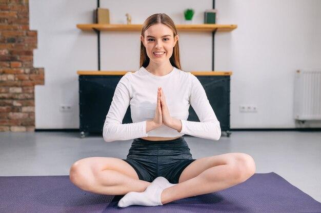 Uma mulher fazendo ioga, sentada em uma posição, as mãos juntas na frente dela