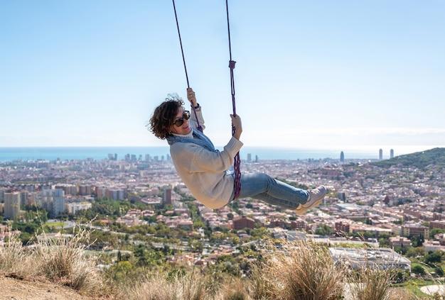 Uma mulher feliz balançando com vista para a cidade
