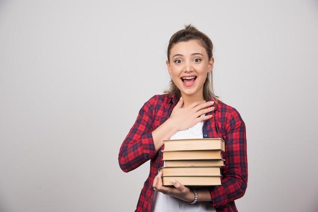 Uma mulher feliz carregando uma pilha de livros em uma parede cinza.