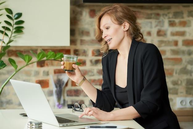 Uma mulher feliz com aparelho trabalhando remotamente em um laptop em uma cozinha. uma senhora com um café discutindo um projeto com colegas em uma videoconferência em casa.