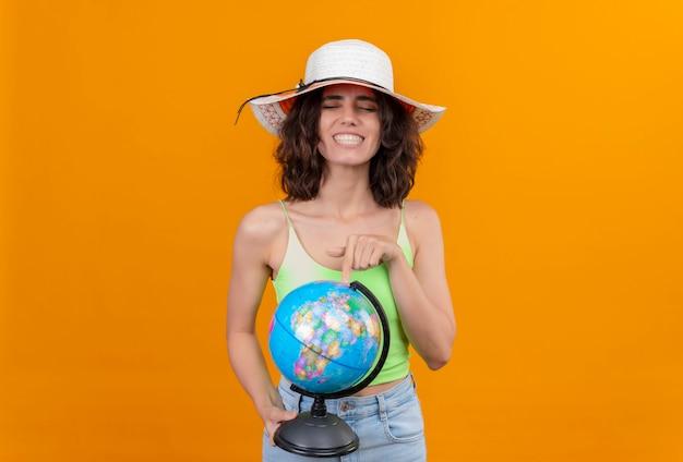 Uma mulher feliz com cabelo curto em um top verde e chapéu de sol apontando para um globo com o dedo indicador