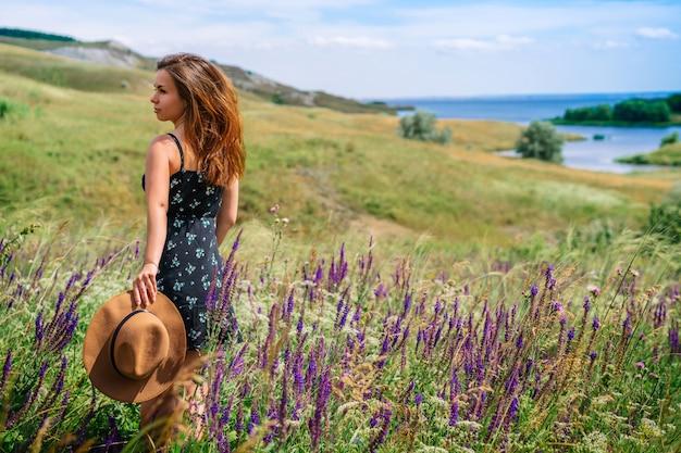 Uma mulher feliz com um vestido segurando um chapéu com fundo de flores silvestres desabrochando e grama em uma área montanhosa
