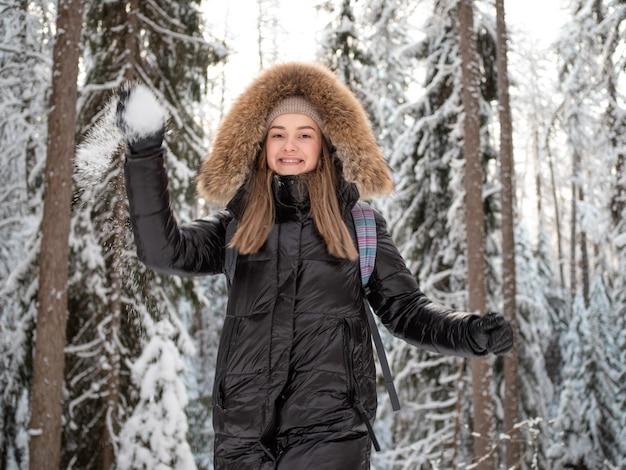 Uma mulher feliz e sorridente com um capuz de pele na cabeça joga neve em você. jogue bolas de neve no inverno na floresta. lazer ao ar livre de inverno.