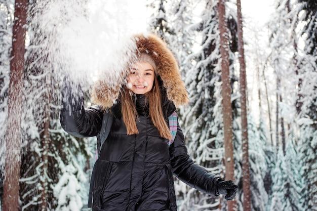 Uma mulher feliz e sorridente com um capuz de pele na cabeça joga neve em você