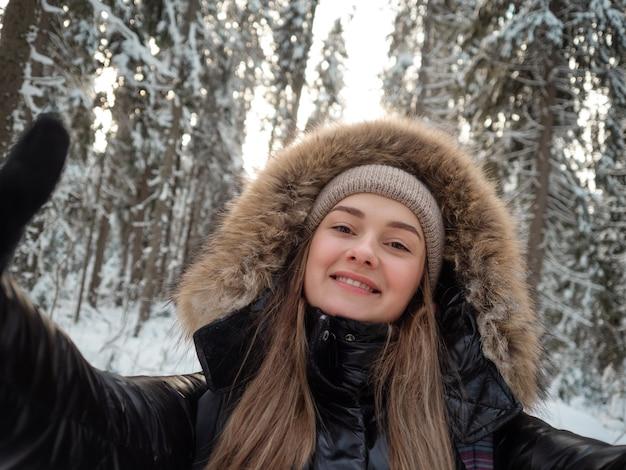 Uma mulher feliz e sorridente com um capuz de pele na cabeça tira uma selfie