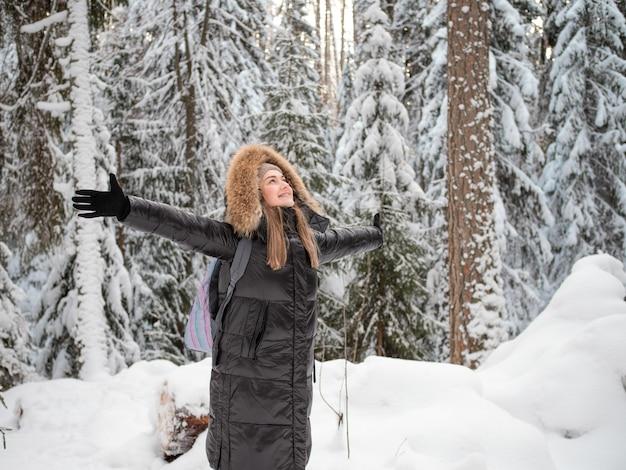 Uma mulher feliz e sorridente com um capuz na cabeça abraça a natureza ao seu redor