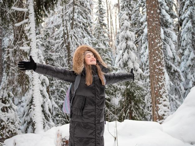 Uma mulher feliz e sorridente com um capuz na cabeça abraça a natureza ao seu redor.