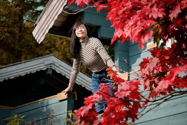 Uma mulher feliz respirando ar fresco no outono, olhos fechados e sorrindo