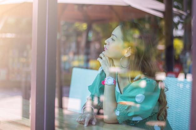 Uma mulher feliz sentada à janela em uma cafeteria e olhando para fora