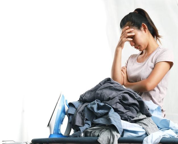 Uma mulher fica com dor de cabeça ao ver uma pilha de roupas e um ferro elétrico.