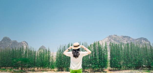 Uma mulher fica de pé para ver a vista das árvores e montanhas de férias