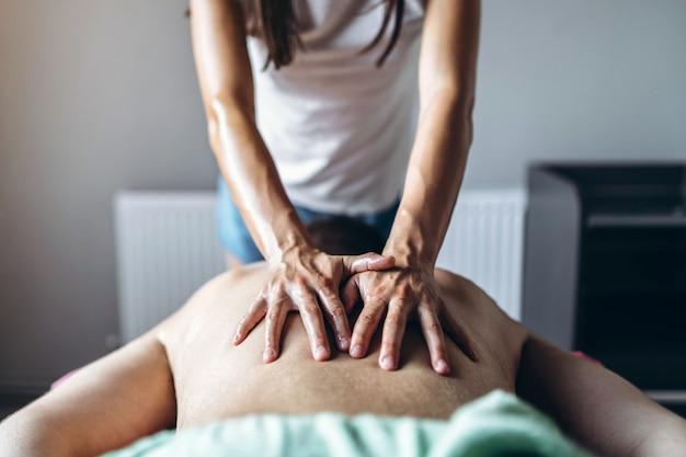 Uma mulher fisioterapeuta fazendo massagem nas costas para um homem no consultório médico