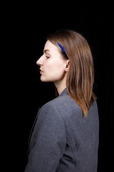 Uma mulher fofa com pele limpa em uma jaqueta cinza de negócios virada de perfil em fundo preto