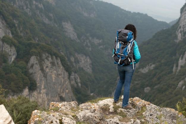 Uma mulher fotografa a paisagem nas montanhas.