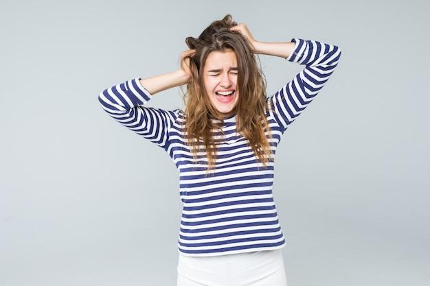 Uma mulher frustrada e irritada está gritando em voz alta e puxando o cabelo dela isolado no fundo branco