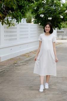 Uma mulher grávida asiática com roupas casuais está caminhando no parque.