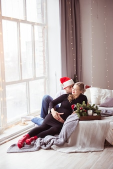 Uma mulher grávida atraente e um homem bonito com um chapéu de papai noel se abraçam em uma cama branca