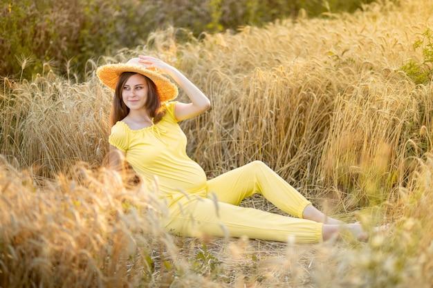 Uma mulher grávida caminha por um campo de trigo no verão