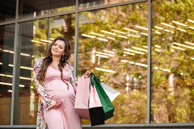 Uma mulher grávida caminhando com pacotes perto de um shopping center. jovem grávida com sacolas de compras em shopping
