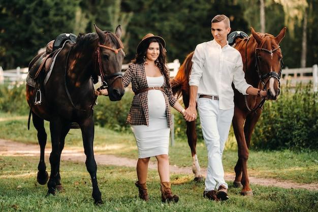 Uma mulher grávida com um chapéu com um homem com roupas brancas, caminhando com cavalos na natureza. uma família que espera por uma criança caminha na floresta.