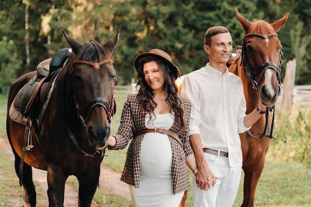 Uma mulher grávida com um chapéu e um homem com roupas brancas caminhando com cavalos na natureza