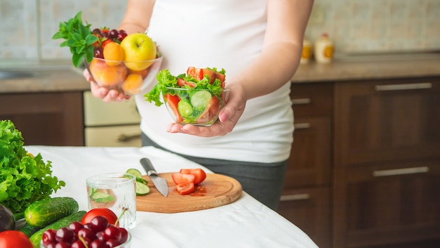 Uma mulher grávida come legumes e frutas