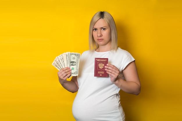 Uma mulher grávida descontente, segurando o passaporte com dinheiro. benefícios para mulheres grávidas, na parede amarela