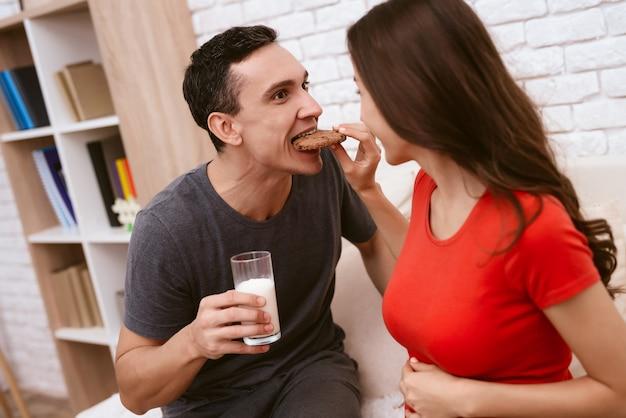 Uma mulher grávida e o marido comem juntos biscoitos.