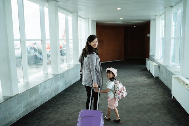 Uma mulher grávida e seu filho andam