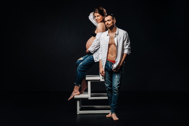 Uma mulher grávida e um homem em uma camisa branca e calça jeans em um estúdio em um fundo preto.