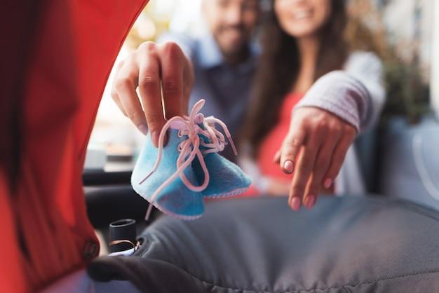 Uma mulher grávida e um homem olham no carrinho de bebê.