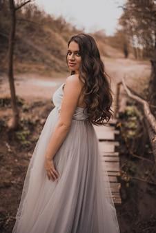 Uma mulher grávida em um vestido longo leve