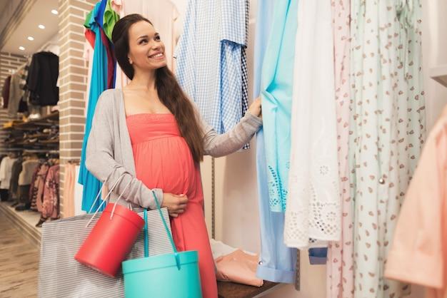 Uma mulher grávida escolhe produtos de bebê na loja