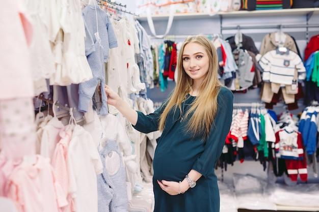 Uma mulher grávida escolhe roupas infantis na loja.