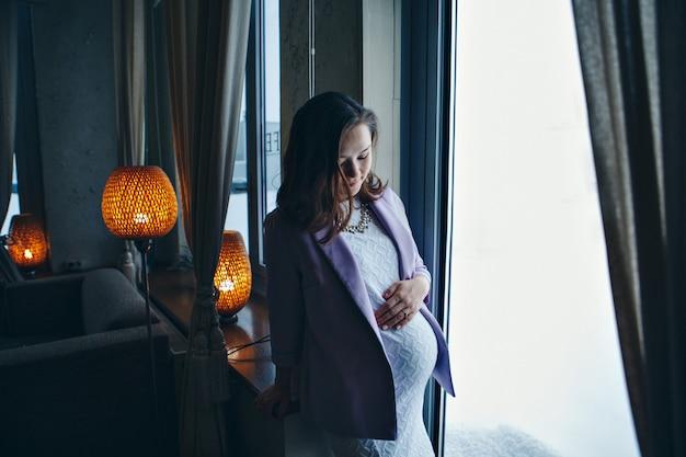 Uma mulher grávida está acariciando seu estômago. uma menina esperando uma criança entra em um shopping center.