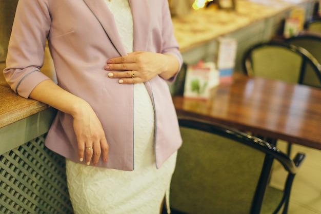 Uma mulher grávida está acariciando seu estômago.