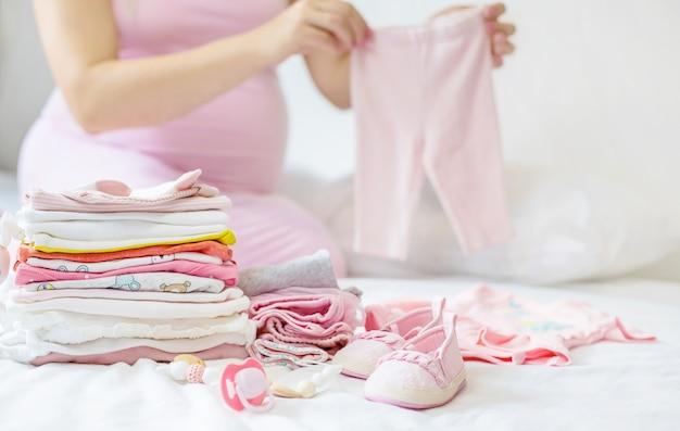 Uma mulher grávida está dobrando coisas de bebê