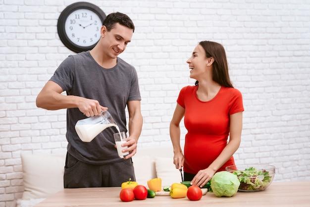 Uma mulher grávida está preparando comida com o marido.