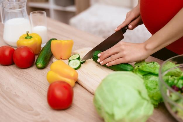 Uma mulher grávida está preparando comida.