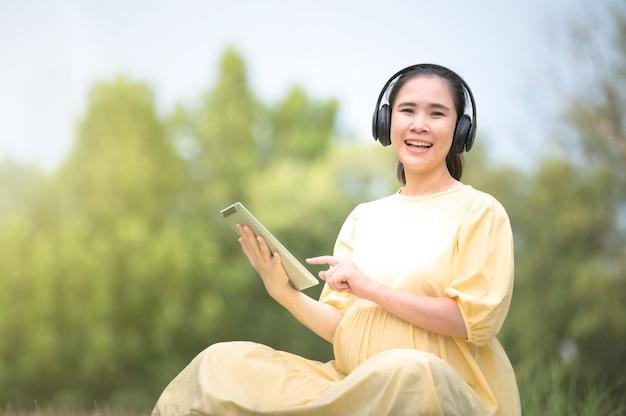 Uma mulher grávida está relaxando no parque e ouvindo música em um tablet, mamãe ouvindo músicas para o feto, grávida perto do parto, mãe e filho