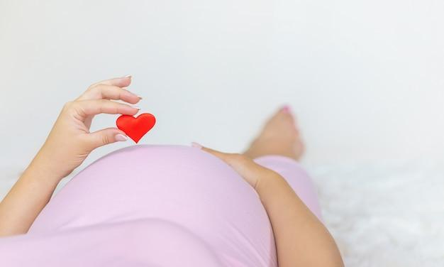 Uma mulher grávida está segurando um coração.