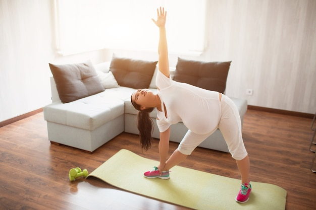 Uma mulher grávida faz exercícios em uma esteira de ioga em casa. gravidez e esportes. oga e pilates para mulheres grávidas. terceiro trimestre de gravidez.