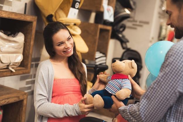 Uma mulher gravida junto com um homem escolhe um urso de peluche.